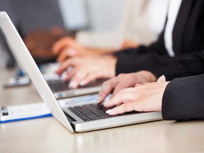 person typing on laptop GlobalNet eLearning consultancy