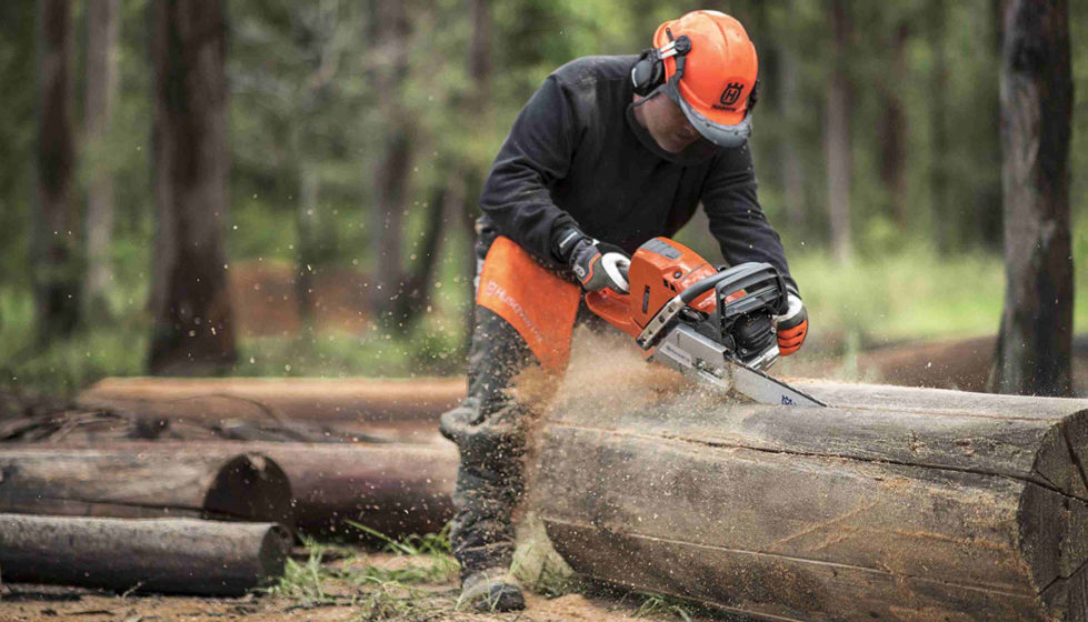 person using husqvarna chainsaw